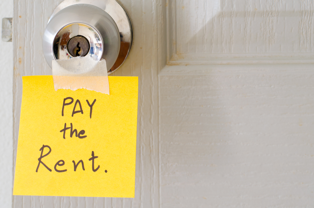 sticky note write a message pay the rent on the latch door