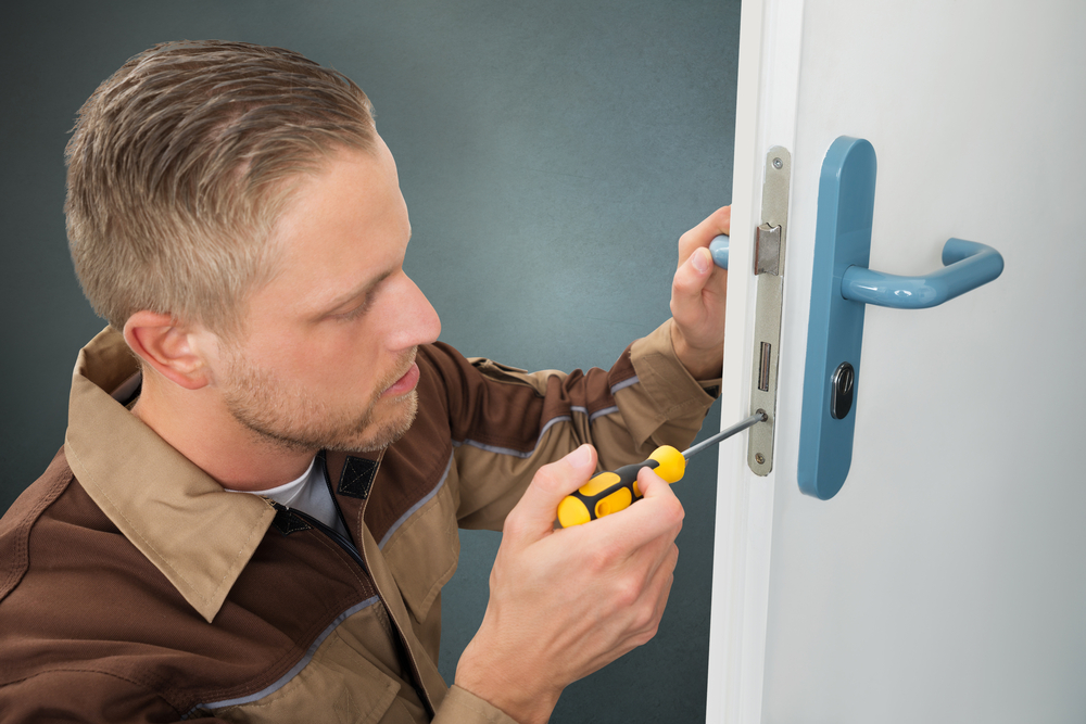 Young Handyman Repair Door Lock