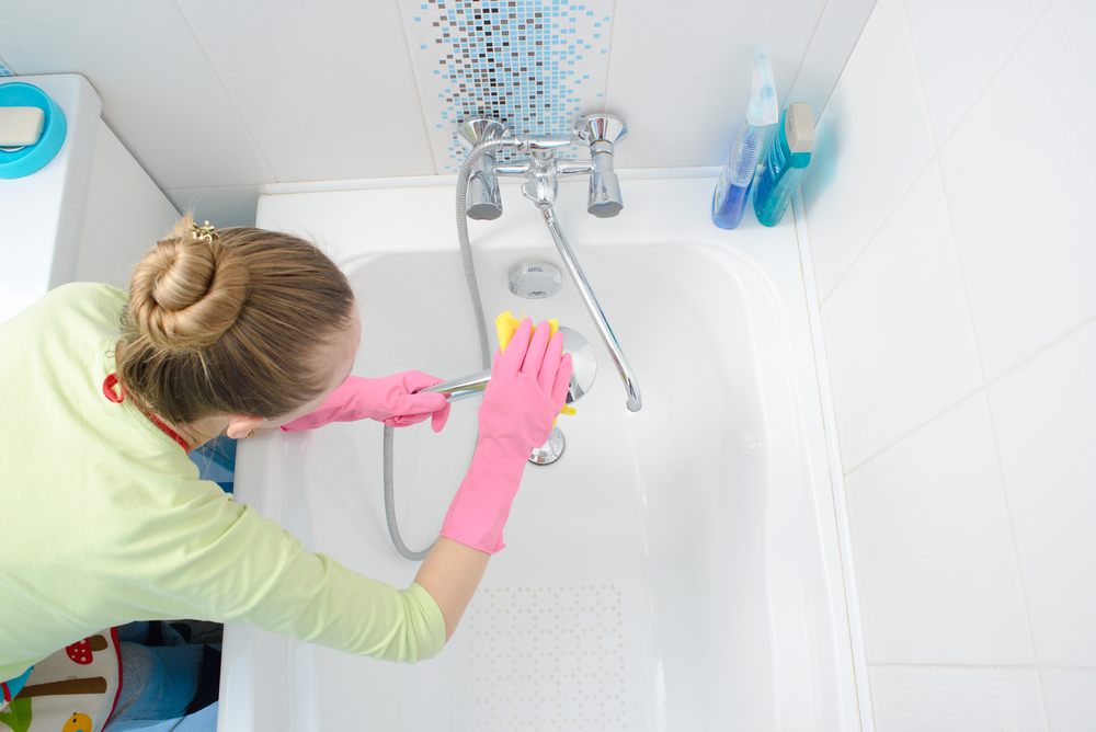 A woman cleaning bath at home
