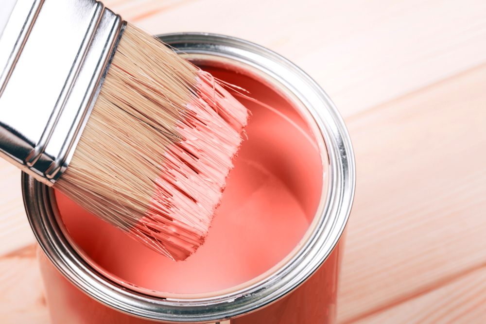 Brush with Living Coral paint on wooden background