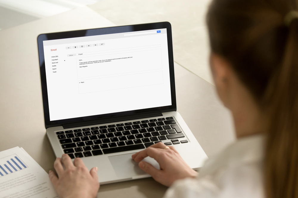 Businesswoman typing e-mail on laptop