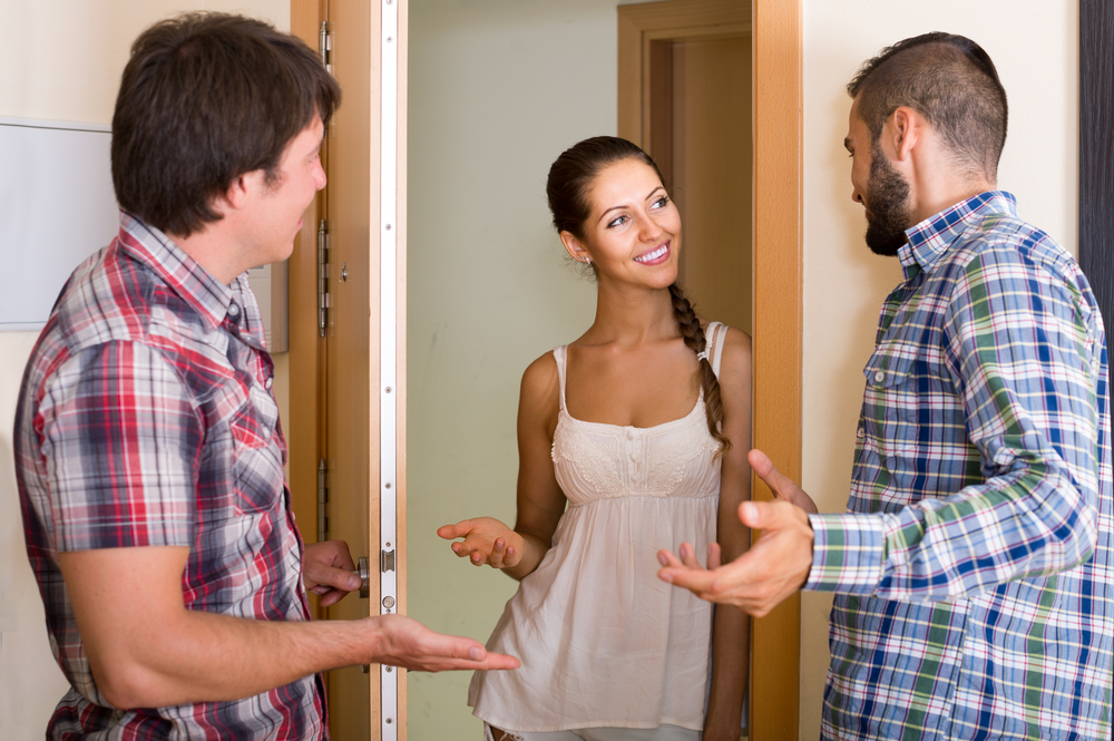 family couple inviting friend in the apartment